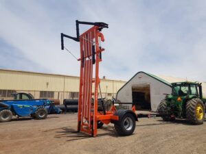 An OzValue Ag brand Bale Stacker, shown in a workyard in an upright position from a front right angle.